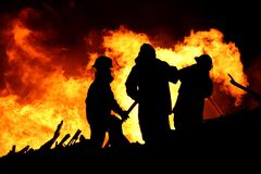 Fire fighters and huge flames. Three firemen fighting a raging fire with huge flames of burning scrap timber Royalty Free Stock Photos