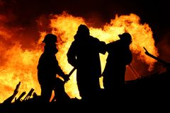 Fire fighters and huge flames. Three firemen fighting a raging fire with huge flames of burning scrap timber Stock Images