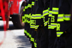 Fire Fighters In a Line. A photo of NYC firefighters line up with the backs of their coats showing Royalty Free Stock Image