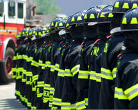 Fire Fighters In a Line. A photo of NYC firefighters line up with the backs of their coats showing