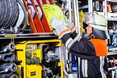 Free Fire Fighters Loading Hoses Into Operations Vehicle Royalty Free Stock Photography - 110870047