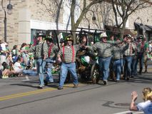 Firefigthers parading during St.Patrick`s Day. Fire Fighters participating in the St. Patrick`s Day Parade every March in Naperville, Illinois. Checkered shirts Royalty Free Stock Image