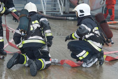 Fire fighters preparing hoses. Firefighters connecting hoses and preparing extinguishing a fire on the scene of an industrial fire accident Royalty Free Stock Images