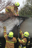 Fire fighters supporting colleague on garage roof Stock Photography
