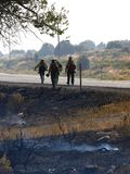 Fire fighters walking. Forest fire fighters walking along a road while fighting a brush fire Stock Images