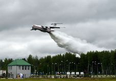 Fire-fighting aircraft IL-76TD drops water over the range of the Noginsk rescue center EMERCOM of Russia at the International Salo stock image