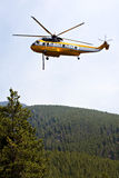 Fire fighting helicopter. With water hose landing to take on water to combat forest fire in Montana Stock Photo