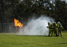 Fire fighting team spraying fire with water. Fire drill for team of firemen using 2 hoses to douse flame with water Royalty Free Stock Photos