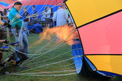 Fire filling hot air balloons held by men and women,Balloon festival,Queensbury,New York,Late Summer,2013 Stock Photography