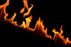 Fire Fire Fire. A wooden bar was burning beyond the dark wall stock image