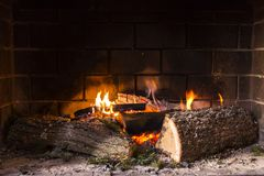Fire in fireplace. Fire burning in fireplace with Christmas tree branches Stock Photos