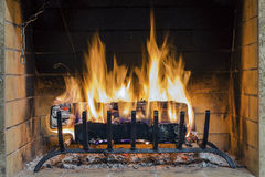 Fire in fireplace. Closeup of firewood burning in fire. Royalty Free Stock Images