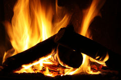 Fire in a fireplace, fire flames on a black background. Texture royalty free stock images