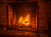A fire in the fireplace with a protective screen. Stock Photo