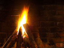 Fire in fireplace, smoked brick wall Royalty Free Stock Photography
