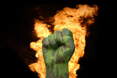 Fire fist with the camouflage texture. Fist with the camouflage texture near the fire on a black background Royalty Free Stock Photo
