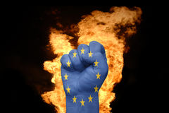 Fire fist with the flag of european union. Fist with the flag of european union near the fire on a black background stock image