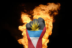 Fire fist with the national flag of antigua and barbuda. Fist with the national flag of antigua and barbuda near the fire on a black background Stock Photos