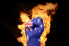 Fire fist with the national flag of australia. Fist with the national flag of australia near the fire on a black background Stock Image