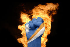 Fire fist with the national flag of Marshall Islands. Fist with the national flag of Marshall Islands near the fire on a black background Royalty Free Stock Photos