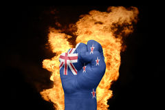 Fire fist with the national flag of new zealand. Fist with the national flag of new zealand near the fire on a black background Royalty Free Stock Photo