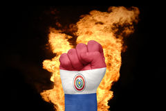 Fire fist with the national flag of paraguay. Fist with the national flag of paraguay near the fire on a black background Stock Photography