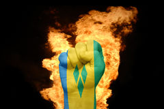 Fire fist with the national flag of Saint Vincent and the Grenadines. Fist with the national flag of Saint Vincent and the Grenadines near the fire on a black Stock Image