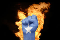Fire fist with the national flag of somalia. Fist with the national flag of somalia near the fire on a black background Stock Photography