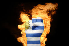 Fire fist with the national flag of uruguay. Fist with the national flag of uruguay near the fire on a black background Royalty Free Stock Photo