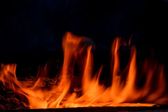 Fire flame bonfire spurts. Red and orange spurts of flame and coal from the bonfire on a black background Royalty Free Stock Image