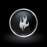Fire flame icon inside round silver and black emblem. Fire symbol with flame icon inside round chrome silver and black button emblem on black background. Vector Royalty Free Stock Photos