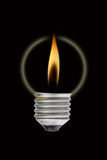 Fire flame out off the light bulb. Fire and smoke in side the light bulb. Concept for energy consumption and environmental awareness Royalty Free Stock Image