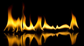 Fire flames on black background. Fire ingniting over reflective surface in a black background Royalty Free Stock Photography