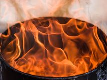 Fire flames on a black background. Burning fire in a barrel against the background of nature Royalty Free Stock Photography