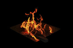 Fire flames on a black background. The flames and embers on the black background Stock Photo