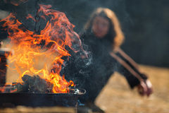 Fire flames on a grill with woman in background relaxing Royalty Free Stock Images