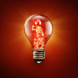 Fire flower inside light bulb. Light bulb with fire flower inside on red Stock Photos