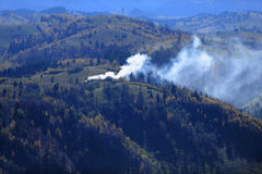 Fire in forested countryside. Aerial view of smoke from fire drifting over forested countryside in autumn, Moieciu, Brasov, Romania Royalty Free Stock Photos