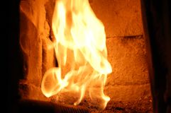 Fire in the furnace. Fireplace. Inside the stove. The old Austrian brick is burnt by the furnace fire. The fire burns against the wall. Inside the fireplace Royalty Free Stock Photos