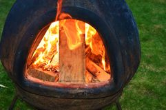 Fire in a garden chimnea. A warming fire glowing inside a garden Chimnea Stock Images