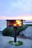 Fire in grill near ocean Royalty Free Stock Photography