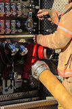 Fire Ground. Firefighter at the pump panel suppling a large volume appliance water delivery system Stock Photography
