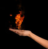 Fire in hand. On black background Royalty Free Stock Photos