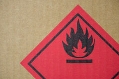Fire hazard symbol on a cardboard box. Close-up detail of a fire hazard warning symbol on a cardboard cargo box containing chemicals stock photo