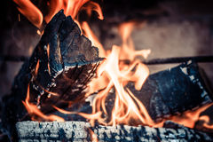 The fire in the hearth. Wooden singe lying together and on fire Royalty Free Stock Image