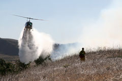 Fire Helicopter. A fire helicopter dropping water on a brush fire as a firefighter watches Stock Images