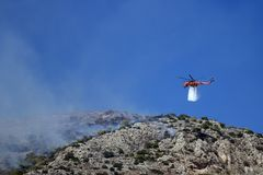 Fire helicopter extinguishes the fire on the hillside . Greece. Fire helicopter extinguishes the fire on the hillside royalty free stock photo