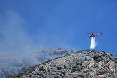 Fire helicopter extinguishes the fire on the hillside . Greece. Stock Images