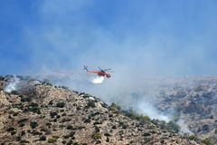 Fire helicopter extinguishes the fire on the hillside . Greece. Fire helicopter extinguishes the fire on the hillside . Greece stock image