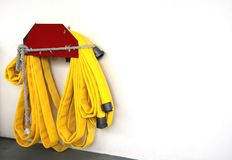 Fire Hose. A yellow fire hose hanging on the wall Royalty Free Stock Photos